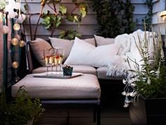 Sofa and footrest with beige cushions, rice paper lights and champagne on a tray