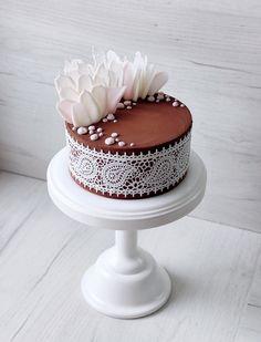 Сочный шоколадный бисквит, серединка из нежного земляничного курда и свежей малины. Покрыт торт бархатным шоколадным кремом, украшен перышками шоколада и сахарным кружевом. Автор Instagram.com/juso.cakes