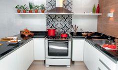 Para dar destaque à estrela do ambiente, o arquiteto propôs um revestimento marcante atrás do fogão. O modelo escolhido, normalmente usado em pisos, surpreendeu dona Nazaré. Projeto de Neto Porpino.