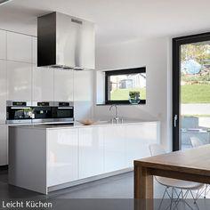 Die offene Küche in Weiß zeichnet sich durch moderne Einheitlichkeit aus. Auch die Abzugshaube fügt sich in den von rechten Winkeln dominierten Look ein. Der …