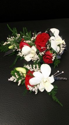 Corsage and bout for prom. White dendrobium orchids and red spray roses. A touch of misty white and rhinestones for bling.