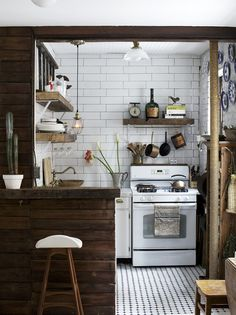 Scandinavian Kitchen - A reclaimed wooden bar in a whitewashed kitchen with subway tile and dark grout.