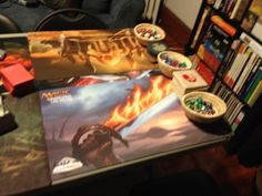 Table in game room set up for MTG with playmats, dice, coasters, etc.