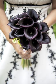 Bride holding a bouquet of purple callas, wearing a wedding dress with dark lace.