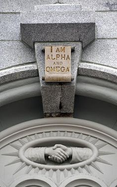 The handclasp symbolizes the hand of fellowship. This feature is located below the all-seeing-eye motif. The alpha-omega inscription reminds us of Jesus Christ's eternal existence (Rev. 1:8).