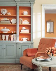 Wyeth Blue + surprising orange/yam in cabinet and chair (espresso legs) + shade of Wyeth in neutral table + sunny neutral walls + another shade of orange/gold in adjoining room + medium beige neutral in carpet + darker wood in floor + toned down warm metal mirror frame, reflecting light