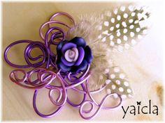 Broche en hilo de aluminio color fucsis-morado y rosa palo.El motivo especial es una flor en fimo de varios tonos de morado,y unas plumitas en moteado blanco y negro.