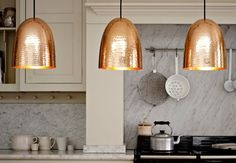 Copper pendant lighting above a kitchen island  Shaker style, marble splashback, kitchen units