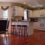 White cabinetry contrasts the richness of the hardwood floors