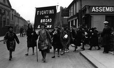 A group of British women on a hunger march in 1930. Their banner reads 'Fighting for Bread and Beans'