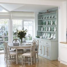 Natural light pours into this country-style dining room. The large duck egg dresser adds elegance to the scheme and is complimented by matching chinaware. The painted-wood dining table and chairs keeps things light and fresh, while a vase with flowers makes for an attractive centrepiece.