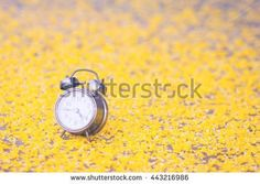 Concept clock and yellow flowers are bright yellow. Selective focus. Vintage Style. And photo filters - stock photo