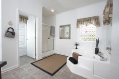 The master bathroom in the Regency Master Suite RF507A - Rockbridge Modular Home. Double sinks, vanity area, soaker tub, walk in shower, separate closet for commode, and more! Check out the floor plan!