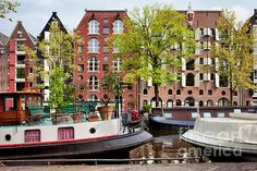 Houseboats and old warehouses converted to apartments blocks along the Brouwersgracht canal (brewers canal) in Amsterdam, Netherlands, North Holland province.
