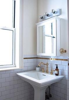A single line of gold tile and distinctive brass faucet elevate an all-white bathroom.