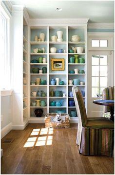 Interior Designer Skip Sroka's vintage McCoy pottery collection displayed on floor-to-ceiling shelves.