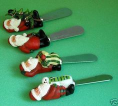Santa Spreaders, set of 4 by Sakura a Division of Oneida (#6814).  Resin top, SS blade, Each Santa wears red suit, hat, black boots and green gloves and holds something: 1) holds snowman w/ green neck scarf; 2) green striped toy bag, right hand over head; 3) ? ; 4) Cmas tree.