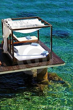 Luxury beds with flowing curtains over tropical water.
