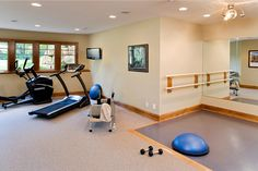 wellness fitness therapy room with room for equipment, weights, mats, balance bar, mirror, windows, WII therapy tv, storage, etc