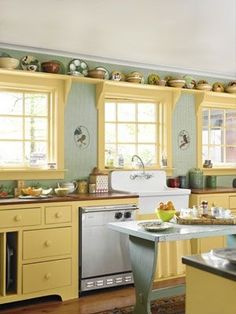 Provence Yellow / Farmhouse Chic  The kitchen gets its warmth from cherry counters, an antique island, gingham-check wallpaper, and an apron sink. Free up cabinet space, and create a clever spot for collectibles, with above-window shelving.    Read more: Kitchen Designs - Pictures of Kitchen Designs and Decorating Ideas - Country Living by Jecka Oh