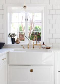 Gorgeous White Farmhouse Sink with Brass Hardware. Click through to the post for a round of up beautiful kitchens and farmhouse sink sources, too!