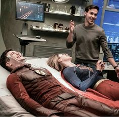 Mon-el laughing with Barry and Kara behind the scenes