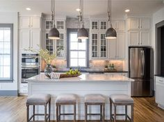 Four backless gray French bar stools sit in front of a white shiplap island topped with a white marble countertop illuminated by three industrial pendants as a smaller pendant hangs in front of a gray trimmed window centered between glass front cabinets fixed above gray marble subway tiles accenting white cabinets fitted with black quartz countertops and nickel knobs.