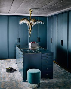 A dressing area off the master suite channels 1920s style with a dramatic navy color scheme, brass hardware, and a vintage chandelier.