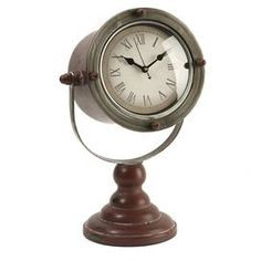 Weathered table clock with a Roman numeral dial.   Product: ClockConstruction Material: Metal, wood and glassColor: Brown and silverFeatures:  Adds chic maritime style to your bedroom, living room, or kitchenAged appearanceExpertly distressed  Accommodates: Batteries - not includedDimensions: 13.75 H x 8 W x 8.25 D