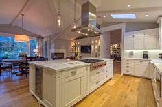 "Traditional Kitchen with Hardwood floors, 42"" Cooktop Island Hood - Stainless, Flat panel cabinets, Limestone Tile, Flush"