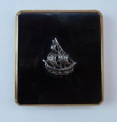This is certainly a most fabulou vintage Statton Powder Compact, dating to the late 1950s or early 1960s.  It is in fantastic condition as you can see in my photographs. It is decoratated on top with a lovely enamel black enamel finish and has a sailing ship added in marcasite in the centre. The black enamel on the llid is without blemishes.  It is designed to take loose powder inside rather than more modern circular pressed powder. It has a metal lid with opens with a little sliding catch…