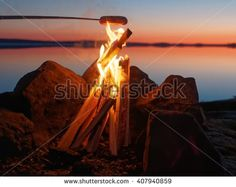 Stock Photo: Sausage grilled on the campfire at sunset. Still water of the lake on the background with atmospheric evening light.
