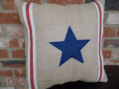 This pillow is made entirely from burlap and has a machine embroidered blue star and red and white striped trim accenting the pillow.