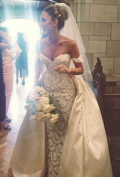 A beautiful bride wearing a couture wedding gown and carrying a pretty bouquet of cascading roses.