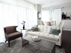 Contemporary open concept living room by LUX Design with white tufted sofa, chrome table, white drapery, and brown chair