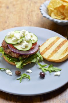 This grilled Greek turkey burger is packed with feta, olives and fresh vegetables and topped with a tangy vinaigrette. Perfect for your summer BBQ #summersoiree