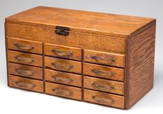 "OAK WATCHMAKER'S STORAGE CABINET, hinged lid concealing a shallow compartment above three stacks of four drawers, original copper pulls impressed ""L.C.R."" on fronts. First quarter 20th century. 6"" H, 5 1/2"" x 11"" Sold $920"