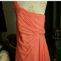 Coral bridesmaid dress  Coral david's bridal bridesmaid dress size 18, the clasp did break off but zips all the way up and stays closed. Dress is not long, bottom has a slant cut to it. One side is longer than the other if your on the shorter side the dress will be long, taller girls most likely fall at your knees or just past! Dress is a one shoulder chiffon ruched at the top and flowey bottom. The dress is an size 18 which runs about a normal size 14/16 since they run small in dresses…