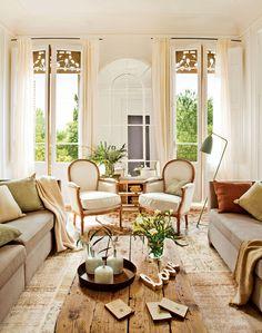 Salón en finca regia con grandes ventanales y distribución simétrica con dos sofás enfrentados y dos butacas