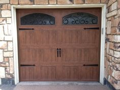 Clopay Gallery Collection steel garage door with Ultra-Grain faux wood finish, decorative wrought iron windows and hardware installed by Castle Improvements in San Diego. www.clopaydoor.com