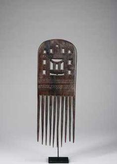 """People: Akan peoples Ghana H: 13 1/2""""  The large flat comb with openwork design and depicting a classical Akan stool in the center. Incised design elements, all tines in fine condition. Fine surface patina."""