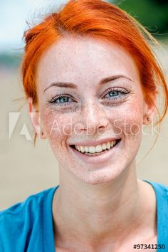 Closeup portrait of a happy beautiful young redhead woman with adorable smile, blue eyes and freckles