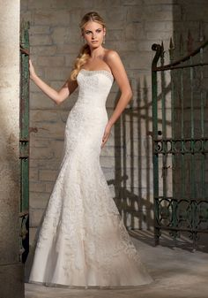 Bold beading trims the strapless neckline and back on this fitted lace bridal…