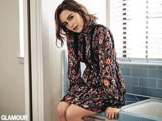 Sitting on a table, Emilia Clarke poses in a long-sleeve Red Valentino dress with floral patterns
