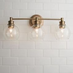 The Volta Glass Collection shines light on minimalism with refreshing, clean design and sleek lines. Available in two finishes, Aged Brass and Polished Nickel, these lighting fixtures allow versatility in designing any space. Clear glass cloche-style shades soften the classic mid-century aesthetic, lending the ambience an ethereal quality. #BathroomLighting