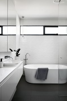 This modern and simple black and white bathroom has slightly textured white tiles, a standalone bathtub and a walk-in glass shower. window Sisalla Interior Design Complete A New Home In Melbourne Bathroom Renos, Laundry In Bathroom, Simple Bathroom, Bathroom Renovations, Bathroom Windows, Family Bathroom, Budget Bathroom, House Design Photos, Modern House Design