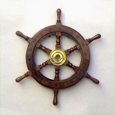 "12"" Nautical Wooden Pirate Wheel. These are wonderful ship's wheels made from solid hardwood teak with brass fastenings, teak wood plugs, a gorgeous dark finish and a solid brass hub keyhole center.  Wheel has a shiny varnish finish, actually nicer than the photos depict.   This is a very solid and attractive wheel. While new, there are inherently, variations in wood grains and colorations from wheel shown. A full 12.5"" across; end of one handle peg to the other, and …"