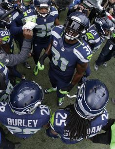 """In this photo made with a fish-eye lens, the Seattle Seahawks """"Legion of Boom"""" defensive players including Kam Chancellor (31) and Richard Sherman (25) huddle together outside the tunnel St. Louis Rams before taking the field, Dec. 28, 2014, in Seattle. AP   Read more here: http://www.newsobserver.com/sports/nfl/carolina-panthers/article10214729.html#storylink=cpy"""