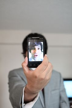 Groomsman in a grey suit taking self portrait with cell phone