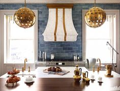 The painterly, watercolor-like look of this kitchen's striking blue subway tile proves an apt foil for marble and metallic details. The perfect backdrop for a gorgeous brass-embellished...